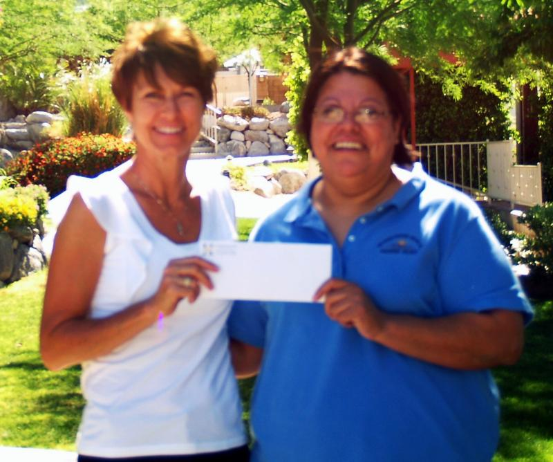 Robin presenting $15,000 to Director Gracie Garcia for Hacienda Valdez